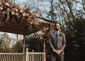 Handsome groom looking so handsome in his nave tween suit with a boutonniere filled with texture and framed by floral gazebo piece.