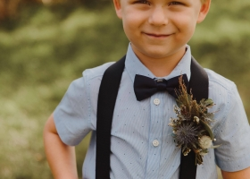 How adorable is this little ring bearer in his suspenders & rustic boutonniere?