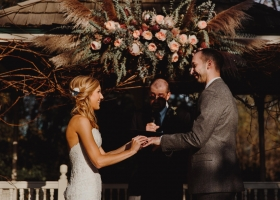 Gazebo backdrop covered in grapevine, garden roses, eucalyptus, grasses and protia was the perfect frame for this Minnetonka Orchard Outdoor wedding.