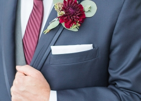 Handsome Groom in Navy Suit at The Muse in Minneapolis wearing a rustic marsala dahlia boutonniere with eucalyptus.