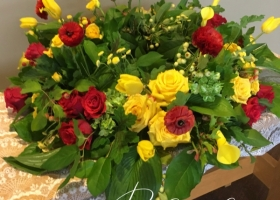 Red and yellow urn spray funeral spray