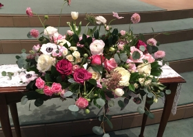 Whymsical pink ranunculus and anenome funeral urn spray