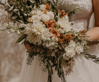 Bride in Designer Wedding Gown holding bouquet in White Blush and Peach