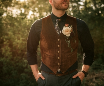 Rustic Groom wearing Rose Boutonniere and Greenery