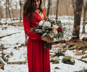 Bride holding rustic bouquet of eucalyptus protea and florals
