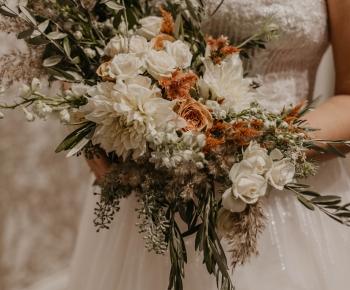 Bride in Designer Wedding Gown holding bouquet in White Blush and Peach