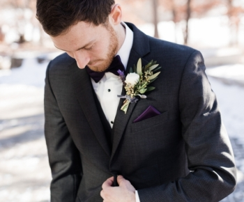 Groom with boutonniere of ranunculus and greenery