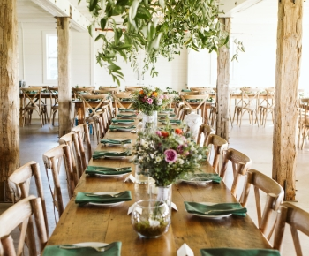 Head table with floral chandelier by Bloomberry Floral